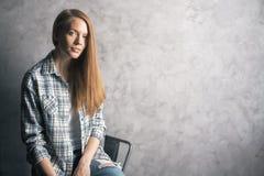 Muchacha que se sienta contra la pared en blanco Imagenes de archivo