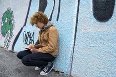 Muchacha que se sienta contra una pared Fotos de archivo