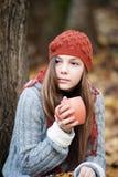 Muchacha que se sienta debajo del árbol con una taza en sus manos Imagenes de archivo