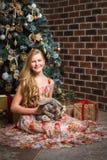 Muchacha que se sienta delante de un árbol de navidad con un conejo Fotografía de archivo