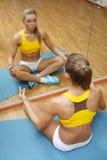 Muchacha que se sienta en actitud de la yoga en la estera del suelo en gimnasia Imagen de archivo