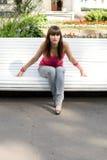 Muchacha que se sienta en banco Foto de archivo libre de regalías
