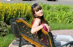 Muchacha que se sienta en banco Imagen de archivo