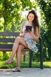 Muchacha que se sienta en banco con el ereader Fotos de archivo libres de regalías