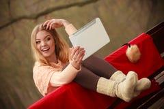 Muchacha que se sienta en banco con la tableta Fotografía de archivo libre de regalías