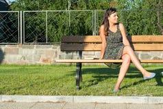 Muchacha que se sienta en banco en el parque que mira lejos Imagenes de archivo