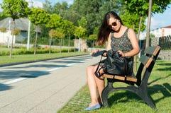 Muchacha que se sienta en banco en mochila de la abertura del parque Fotografía de archivo