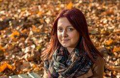 Muchacha que se sienta en banco en parque Imágenes de archivo libres de regalías