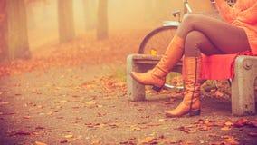 Muchacha que se sienta en banco en parque del otoño Foto de archivo