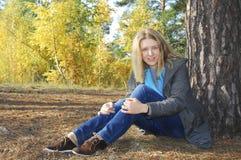 Muchacha que se sienta en bosque del otoño. cerca de un árbol de pino. Foto de archivo libre de regalías