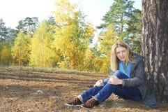 Muchacha que se sienta en bosque del otoño. cerca de un árbol de pino. Imágenes de archivo libres de regalías