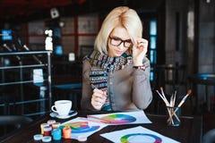 Muchacha que se sienta en café con la taza de café y de dibujo Fotografía de archivo libre de regalías