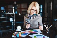 Muchacha que se sienta en café con la taza de café y de dibujo Fotografía de archivo