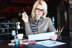 Muchacha que se sienta en café con la taza de café y de dibujo Foto de archivo libre de regalías