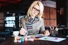 Muchacha que se sienta en café con la taza de café y de dibujo Imagenes de archivo