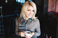Muchacha que se sienta en café con la taza de té y de sonrisa Foto de archivo