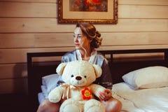 Muchacha que se sienta en cama con el juguete suave Foto de archivo
