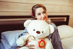 Muchacha que se sienta en cama con el juguete suave Foto de archivo libre de regalías
