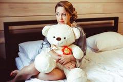 Muchacha que se sienta en cama con el juguete suave Imagen de archivo libre de regalías