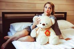 Muchacha que se sienta en cama con el juguete suave Fotos de archivo libres de regalías
