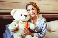 Muchacha que se sienta en cama con el juguete suave Fotografía de archivo libre de regalías