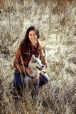 Muchacha que se sienta en campo con el perro esquimal y sonrisas Fotografía de archivo