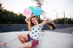 Muchacha que se sienta en carro con los globos y la botella de champán Fotos de archivo libres de regalías