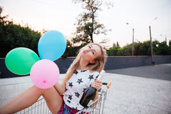Muchacha que se sienta en carro con los globos y la botella de champán Fotos de archivo