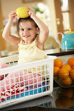 Muchacha que se sienta en cesta de lavadero con el limón Foto de archivo libre de regalías