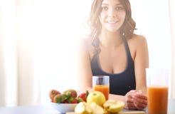 Muchacha que se sienta en cocina en el escritorio con la fruta y el jugo de los vidrios Imágenes de archivo libres de regalías