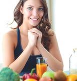 Muchacha que se sienta en cocina en el escritorio con la fruta y el jugo de los vidrios Foto de archivo libre de regalías