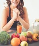 Muchacha que se sienta en cocina en el escritorio con la fruta y los vidrios con el jugo Fotografía de archivo libre de regalías
