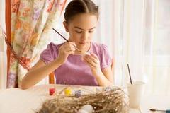 Muchacha que se sienta en cocina y el huevo de Pascua de pintura Imagen de archivo libre de regalías
