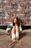 Muchacha que se sienta en dormitorio y la lectura Fotografía de archivo libre de regalías