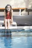 Muchacha que se sienta en The Edge de la piscina Fotografía de archivo libre de regalías