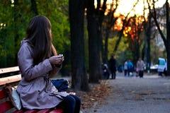 Muchacha que se sienta en el banco en parque por la tarde Foto de archivo