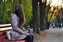 Muchacha que se sienta en el banco en parque por la tarde Imagen de archivo