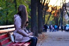 Muchacha que se sienta en el banco en parque por la tarde Fotografía de archivo libre de regalías