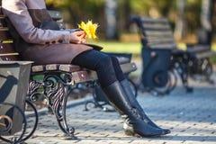 Muchacha que se sienta en el banco en el otoño en parque Imagenes de archivo
