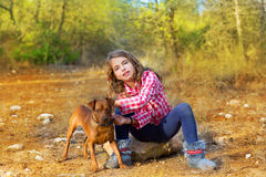 Muchacha que se sienta en el bosque del pino que sostiene el pequeño perro Imágenes de archivo libres de regalías