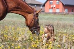 Muchacha que se sienta en el caballo de la tierra y de la castaña que se coloca cerca Fotos de archivo libres de regalías