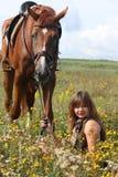 Muchacha que se sienta en el caballo de la tierra y de la castaña que se coloca cerca Fotografía de archivo libre de regalías
