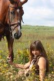 Muchacha que se sienta en el caballo de la tierra y de la castaña que se coloca cerca Fotografía de archivo