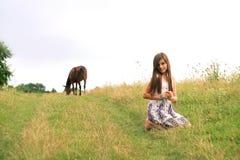 Muchacha que se sienta en el camino rural Imágenes de archivo libres de regalías