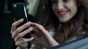 Muchacha que se sienta en el coche usando el teléfono, sonriendo y mirando a través de la ventana metrajes