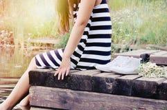 Muchacha que se sienta en el embarcadero en el lago en el día de verano caliente soleado, va Imágenes de archivo libres de regalías