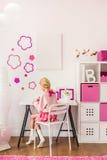 Muchacha que se sienta en el escritorio Foto de archivo libre de regalías
