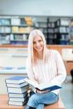Muchacha que se sienta en el escritorio con la pila de libros Fotografía de archivo libre de regalías