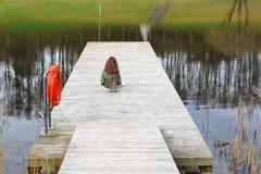 Muchacha que se sienta en el lago de desatención de la cubierta de madera Fotos de archivo