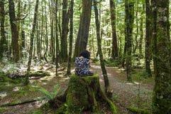 Muchacha que se sienta en el medio de un bosque foto de archivo